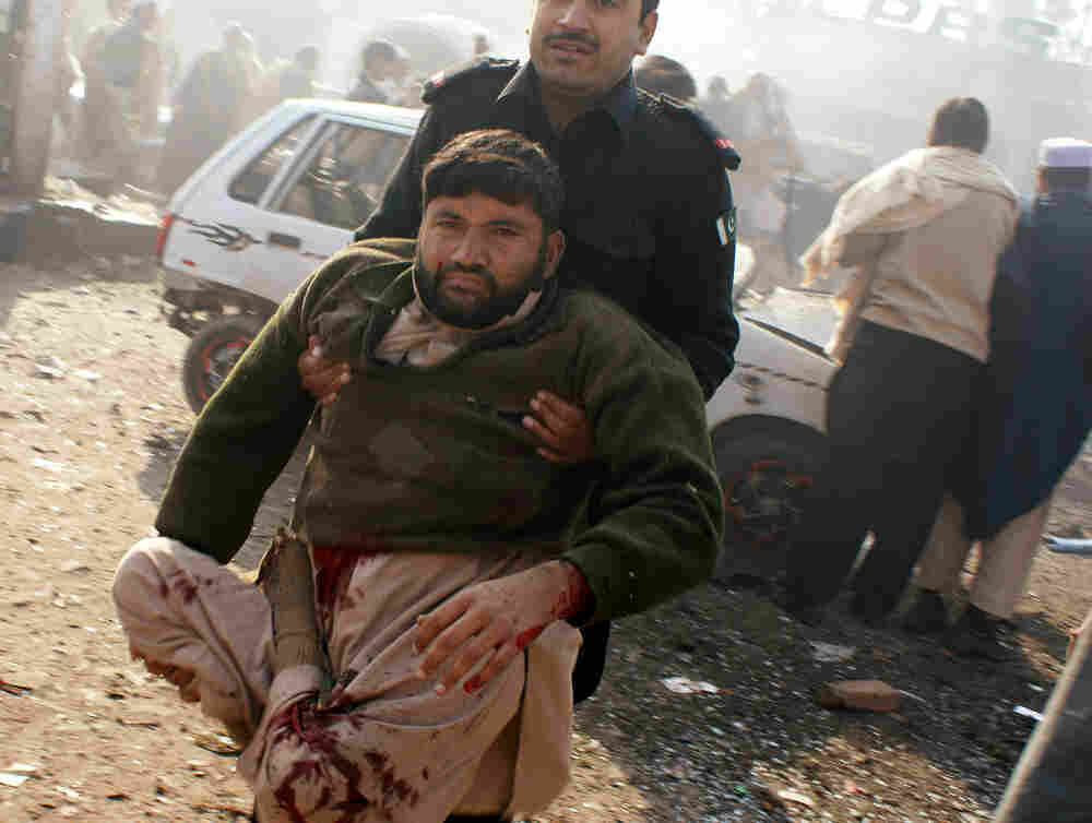 A member of the security personnel carries an injured person to a vehicle after an explosion in Pakistani tribal area of Khyber near Peshawar, Pakistan on Tuesday.