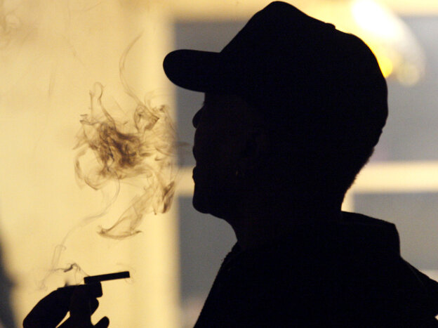 An unidentified man smokes medical marijuana during a karaoke night at the Cannabis Cafe in Portland, Ore., last May.