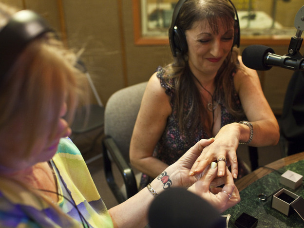 Janice Oeffner places a ring on the finger of Dawn Williams during an on-air proxy wedding between Williams and a Texas inmate. On-air proxy weddings have become so common that <em>The Prison Show</em> has a wedding coordinator to help guide couples through the paperwork.