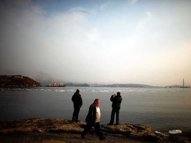 Compared to many of the dynamic economies in Asia, development is Russia's Far East is limited. Here, men wait for a ferry to take them to Russky Island just off Vladivostok, on Russia's Pacific Coast. In the background, a bridge to the island is being built.
