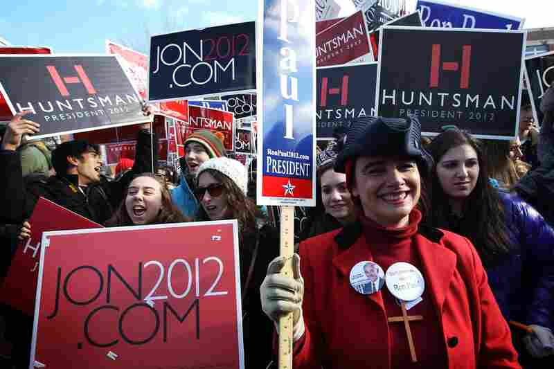 A supporter of Ron Paul stands in front of a group of Jon Huntsman supporters outside a polling place in Manchester.