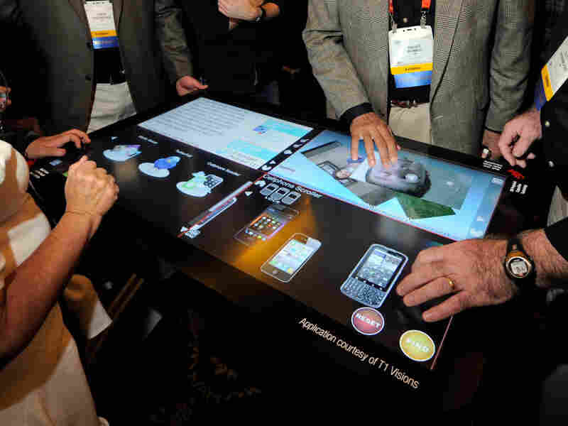 Attendees try a prototype 3M Touch Systems projected capacitive display at the Consumer Electronics Show in Las Vegas. Analysts say the way we interact with computers and other devices will be radically different in a few decades.