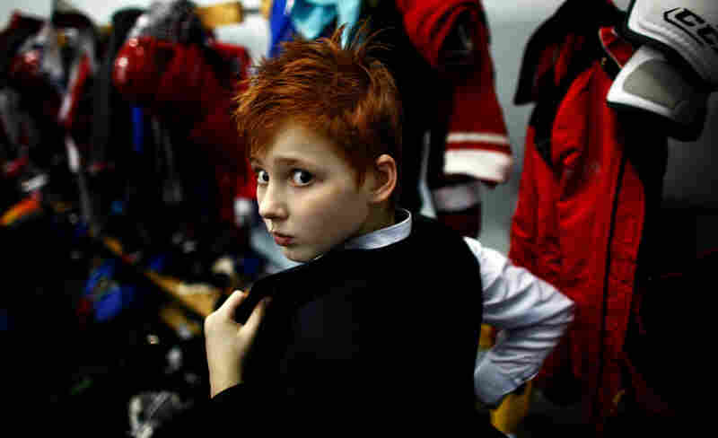 A boy in a youth hockey training program changes out of his uniform after practice at an ice rink in Yaroslavl, Russia. In September, a plane crash killed every member of Yaroslavl's professional hockey team, Lokomotiv.