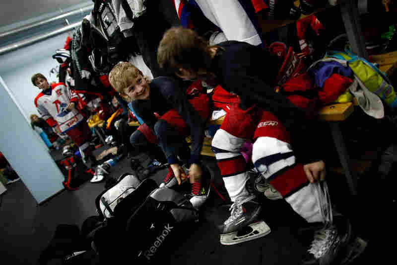 The young hockey players change out of their uniforms after practice.