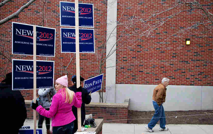 A man walks past campaign workers touting their candidates during voting in the New Hampshire primary, at Webster Elementary School in Manchester on Tuesday.