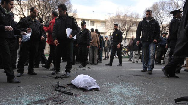Iranian security forces inspect the site where a magnetic bomb attached to a car by a motorcyclist exploded outside a university in Tehran on Wednesday, killing nuclear scientist Mostafa Ahmadi Roshan. (AFP/Getty Images)