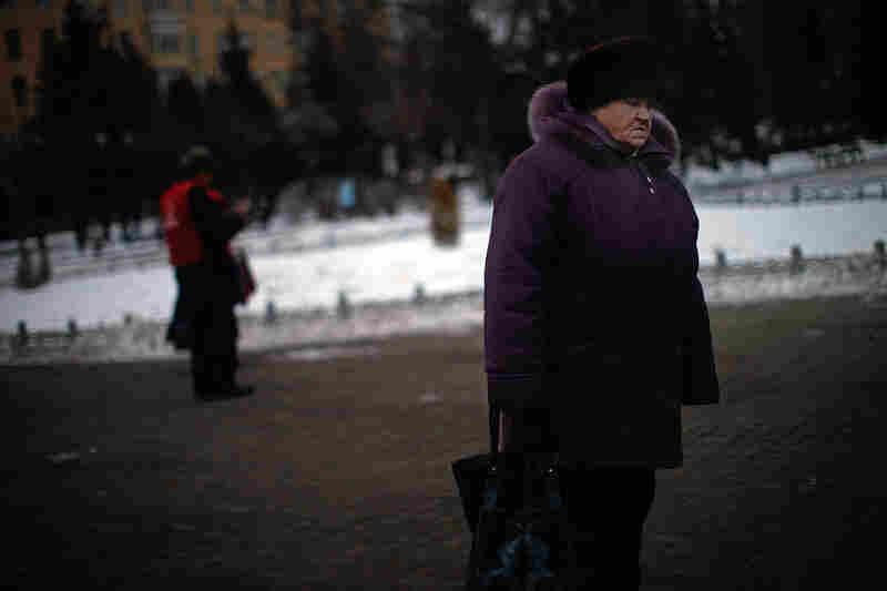 An old woman walks through a park in Rybinsk.