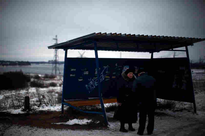 People wait at an open-air bus shelter outside of Rybinsk.