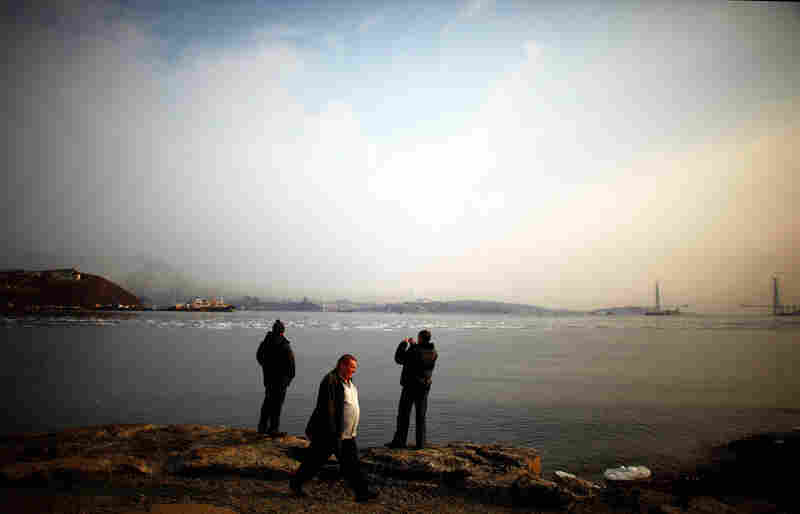 Three men wait for a ferry to take them across the water to Russky Island, just across from Vladivostok, the port city in Russia's