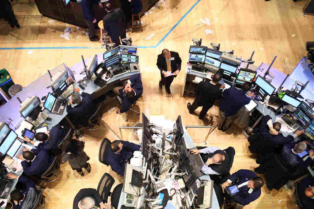 Traders work on the floor of the New York Stock Exchange in December. In the past year, banks in New York and around the country have announced tens of thousands of job cuts, as there isn't the same need for some financial services as before.