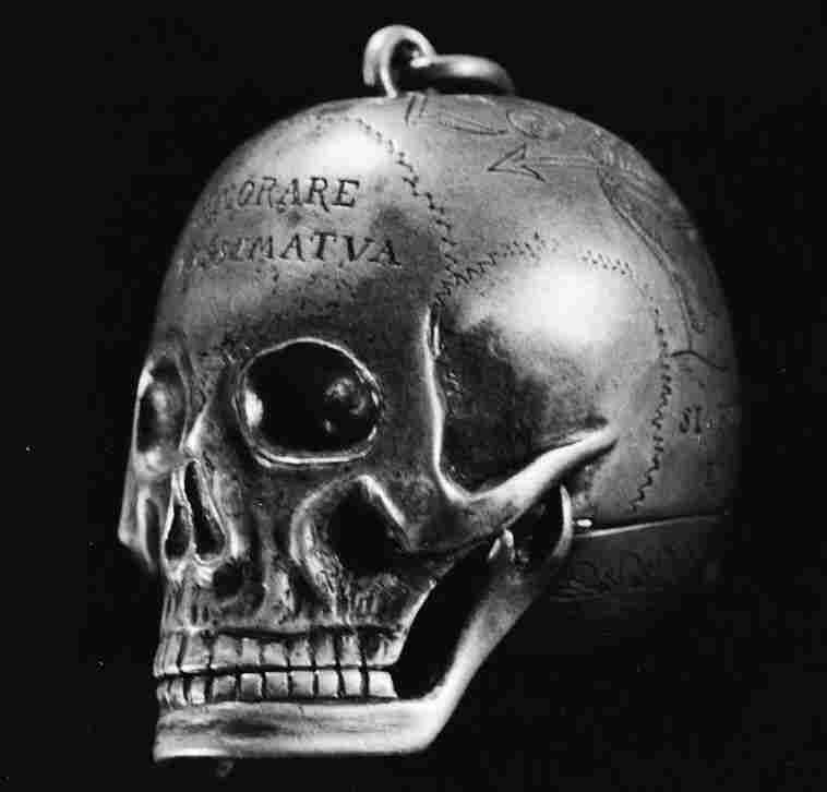 An engraved metal skull which once belonged to Mary, Queen of Scots, bearing inscriptions relating to death. The skull unhinges to expose a watch.