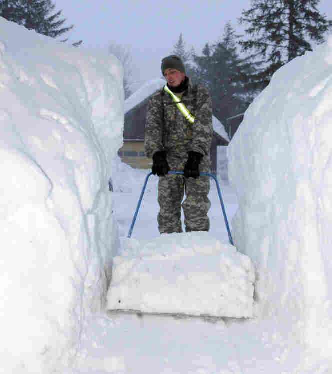 A member of the Alaska National Guard clearing a walkway in Cordova earlier this week.