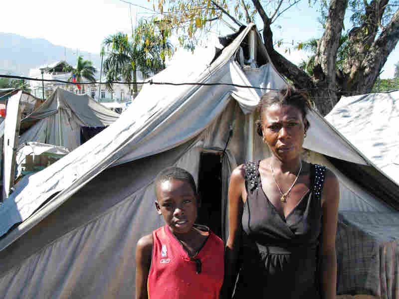 "Gerline Rousole, 22, stands next to her son, Savoiu, 7, in Place Pigeon, a displaced-person camp outside the National Palace in Port-Au-Price. Both of Rousole's parents died in the Jan. 12, 2010, earthquake. ""If my parents were still alive, I wouldn't be here,"" she says."