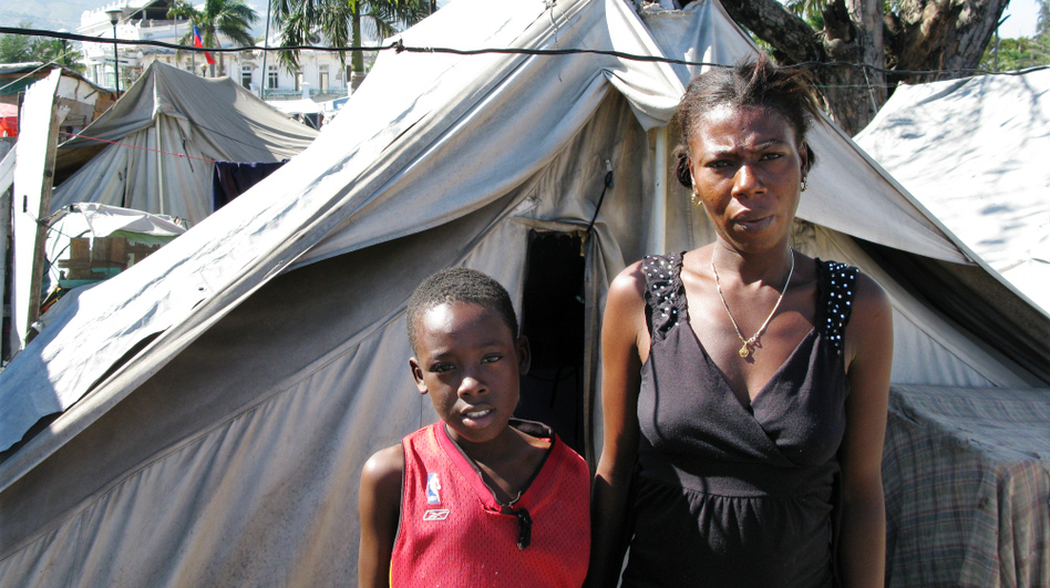 "Gerline Rousole, 22, stands next to her son, Savoiu, 7, in Place Pigeon, a displaced-person camp outside the National Palace in Port-Au-Price. Both of Rousole's parents died in the Jan. 12, 2010, earthquake. ""If my parents were still alive, I wouldn't be here,"" she says.  (NPR)"