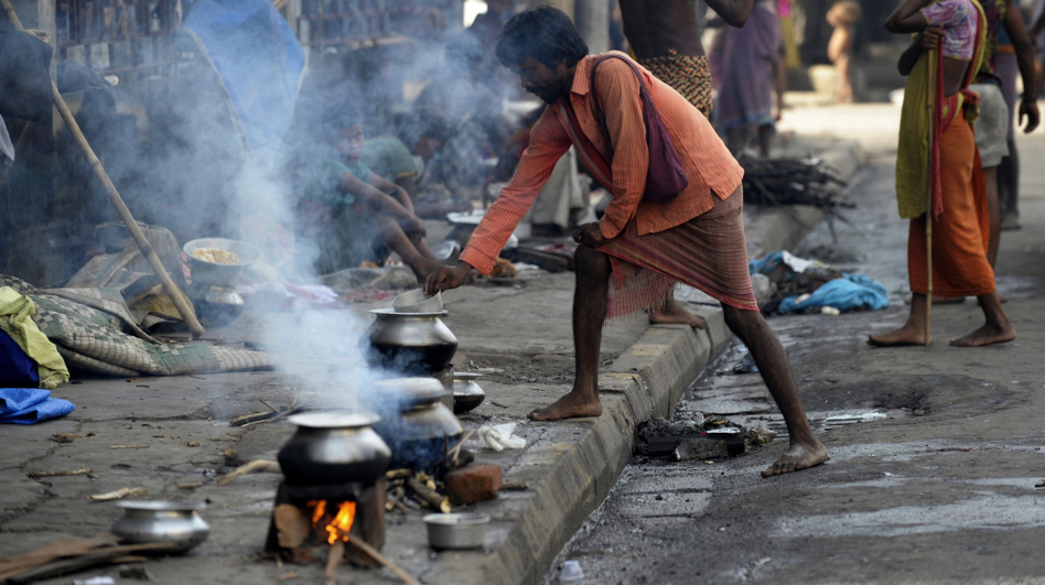 An Indian street dweller prepares food on the streets of Kolkata. A growing number of scientists say that reducing black carbon — mostly soot from burning wood, charcoal and dung — would have an immediate and powerful impact on climate.