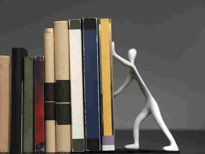 A bookend shaped like a person, holding up a row of books