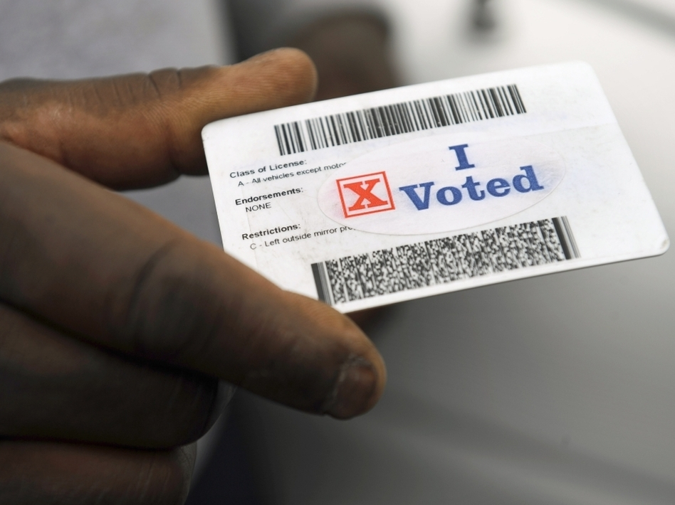 """Verdell Winder of Washington holds up his driver's license showing his """"I Voted"""" sticker after voting on Election Day on Nov. 4, 2008."""