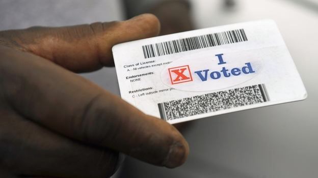"""Verdell Winder of Washington holds up his driver's license showing his """"I Voted"""" sticker after voting on Election Day on Nov. 4, 2008. (AP)"""