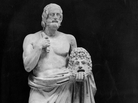 "A statue of Euripides (480-406 B.C.), Greek philosopher and dramatist, holding a ""tragic"" mask."