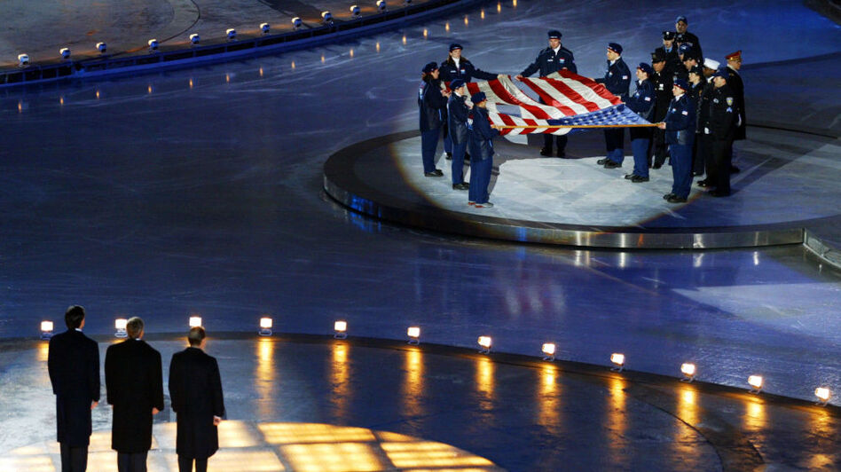 At the opening ceremony of the 2002 Winter Olympics in Salt Lake City, Mitt Romney (left) stands with President George W. Bush (center) and International Olympic Committee President Jacques Rogge (right) in front of the American flag that flew at the World Trade Center before the Sept. 11 terrorist attacks.  (AFP/Getty Images)