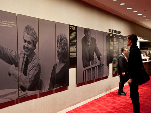 In better days, a New York City Opera attendee takes in a display about the beleagured company's rich history.