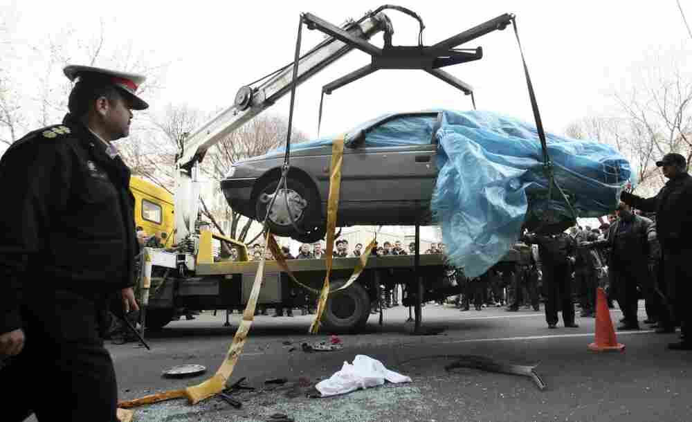 People gather around a car as it is removed by a mobile crane in Tehran, Iran. The car was being driven by Iranian nuclear scientist Mostafa Ahmadi Roshan when it was targeted by a bomb Wednesday. Roshan was killed in the blast.