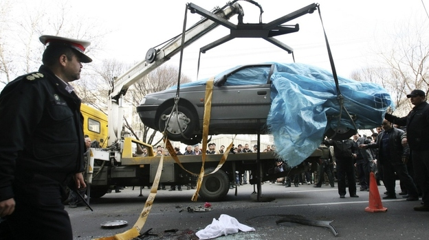 People gather around a car as it is removed by a mobile crane in Tehran, Iran. The car was being driven by Iranian nuclear scientist Mostafa Ahmadi Roshan when it was targeted by a bomb Wednesday. Roshan was killed in the blast. (AP)