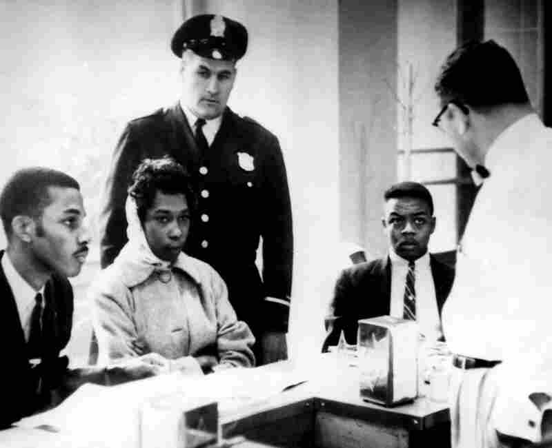 Victor Cobb (right), the manager of a dining room in Atlanta's Trailways Bus Terminal, asks African-American demonstrators to leave his lunch counter on March 16, 1960. The demonstrators stared at him in silence and refused to leave; they were then arrested.