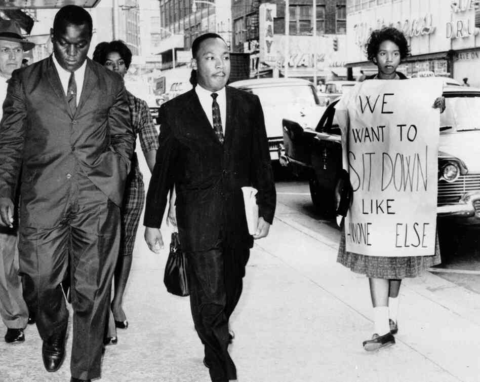 The Rev. Martin Luther King Jr. is escorted by an Atlanta police officer (left rear) after being arrested following demonstrations against lunch-counter segregation, Oct. 9, 1960.