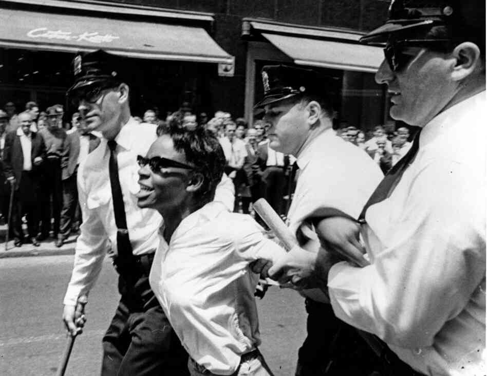 Bertha Gilbert, 22, is led away by police after she tried to enter a segregated lunch counter in Nashville, Tenn., on May 6, 1964.