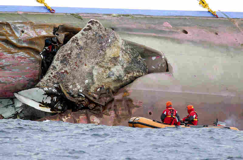 A large rock emerges from the side of the luxury liner a day after the ship ran aground. Crews are working to remove fuel from the ship in an effort to preserve a stretch of Mediterranean described as the biggest designated marine park in Europe.