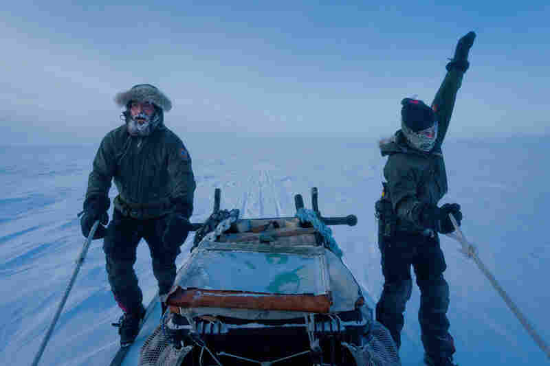Rotating their arms to stay warm, Jesper Olsen (right) and Rasmus Jergensen ski beside a sled full of supplies: rifles, a radio, first aid, a tent, sleeping bags, a big map, and plenty of dog food.