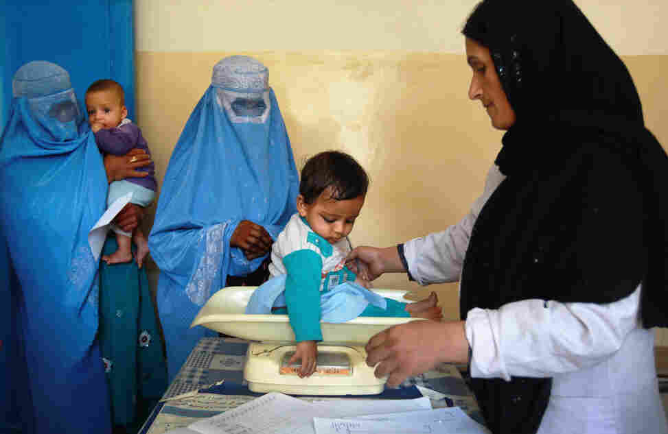 A nurse weighs an Afghan child at a U.S.-funded clinic in Farza, Afghanistan, in September. A new U.S.-sponsored survey shows dramatic gains in life expectancy and other aspects of health care in Afghanistan. But some experts are questioning the accuracy of the results.