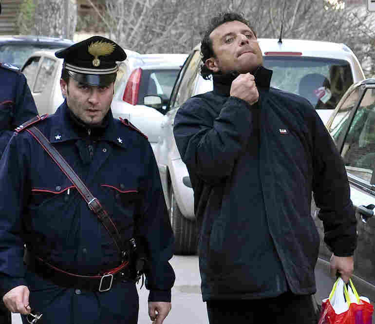 Capt. Francesco Schettino (right) is taken into custody by police in Porto Santo Stefano, Italy, on Jan. 14. Schettino was released Tuesday and is under house arrest in southern Italy. He is being investigated on possible manslaughter charges and abandoning his ship.