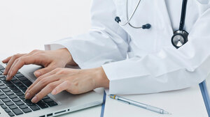 A doctor types at a computer.