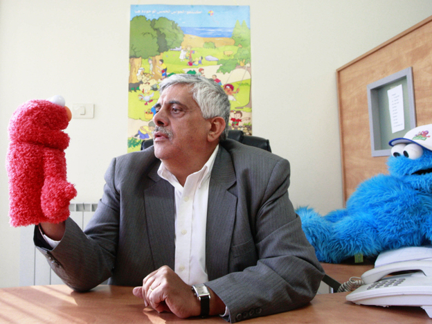 Daoud Kuttab, executive producer of <em>Shara'a Simsim</em>, the Palestinian version of <em>Sesame Street</em>, holds a Muppet at his office in the West Bank city of Ramallah earlier this month. The producers say they have been forced to put production for the 2012 season on hold because of a funding freeze by the U.S. Congress.