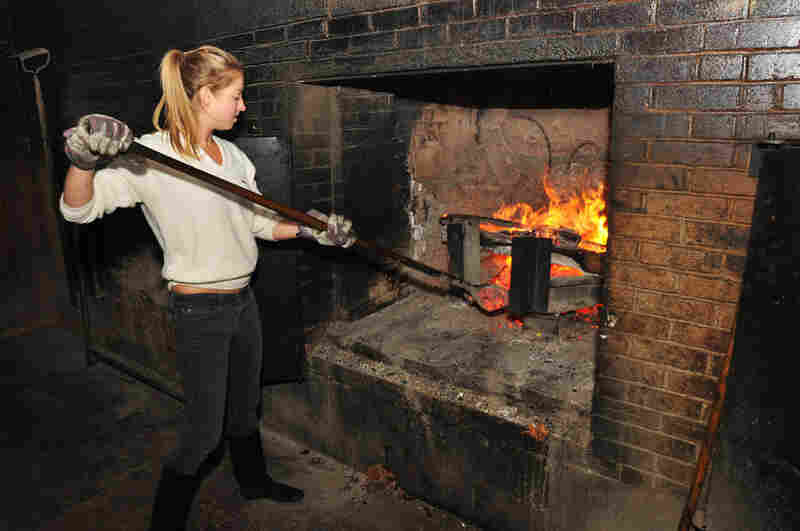 Molly, who left her job as a chef at a Michelin-starred French restaurant in New York City, hoped to learn from the masters of barbecue. Molly feeds hickory embers to the fire at 30-minute intervals at Allen and Son BBQ in Chapel Hill, N.C.