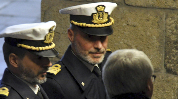 Italian coast guard Capt. Gregorio De Falco (center) has become a national hero for ordering the captain of a sinking cruise liner to get back onboard and oversee the ship's evacuation. Here, De Falco arrives in court for a hearing on Tuesday.  (AP)