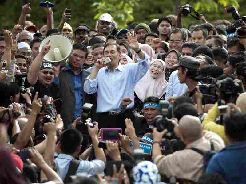Malaysian opposition leader Anwar Ibrahim (center), accompanied by his wife, Wan Azizah (center right), speaks to his supporters in Kuala Lumpur on Jan. 9 after his acquittal. Anwar is a former student activist — and many say Adam is feared by the government as much as Anwar was.