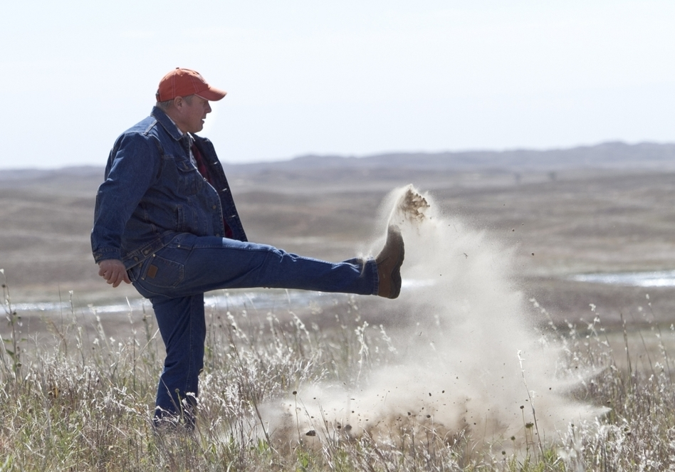 Atkinson, Neb., rancher Bruce Boettcher, who opposes the Keystone XL pipeline, kicks up sand on his land, to demonstrate the fragility of the sandhills near the planned route of the pipeline.