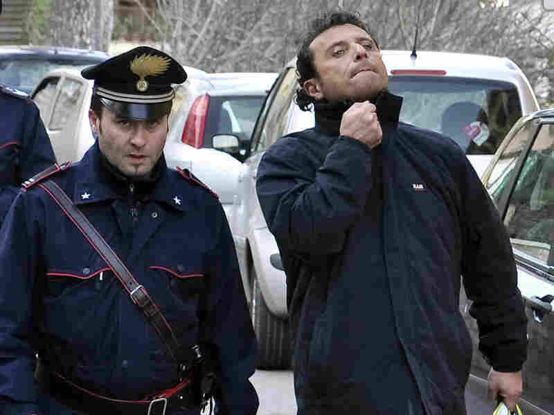 Francesco Schettino, right, the captain of the Costa Concordia cruise liner, has been accused of manslaughter and abandoning the ship. Here he's shown in police custody in Porto Santo Stefano, Italy on Saturday He is now under house arrest.