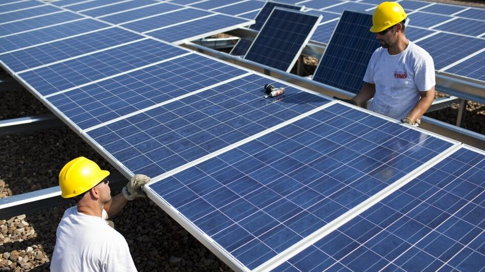 Contractors with SunEdison install more than 1,000 Chinese-made solar panels on top of a Kohl's Department Store in Hamilton Township, N.J., in 2010. Energy generated by the solar system will cut the store's usage, on average, by 25 to 30 percent. (Robert Nickelsberg/Getty Images)