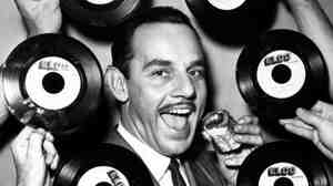 "Band leader Johnny Otis poses for a portrait in surrounded by ""The Jelly Roll"" records in 1947."