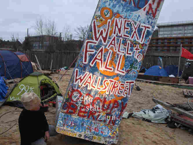 An Occupy protester tips a styrophoam, mock-section of the Berlin Wall covered with graffiti referring to Wall Street on Jan. 6, 2012 in Berlin, Germany. Opposition to Citizens United seeks to reverse the decision prohibiting limits on some campaign contributions.