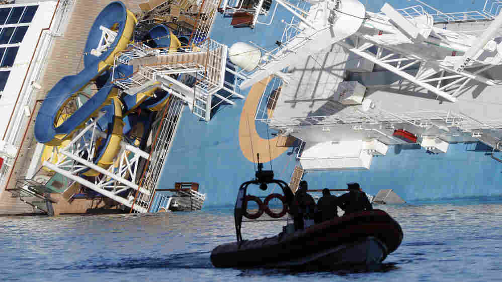A coast guard boat passes the Costa Concordia, as the cruise liner lies aground in front of the harbor of Giglio Island.