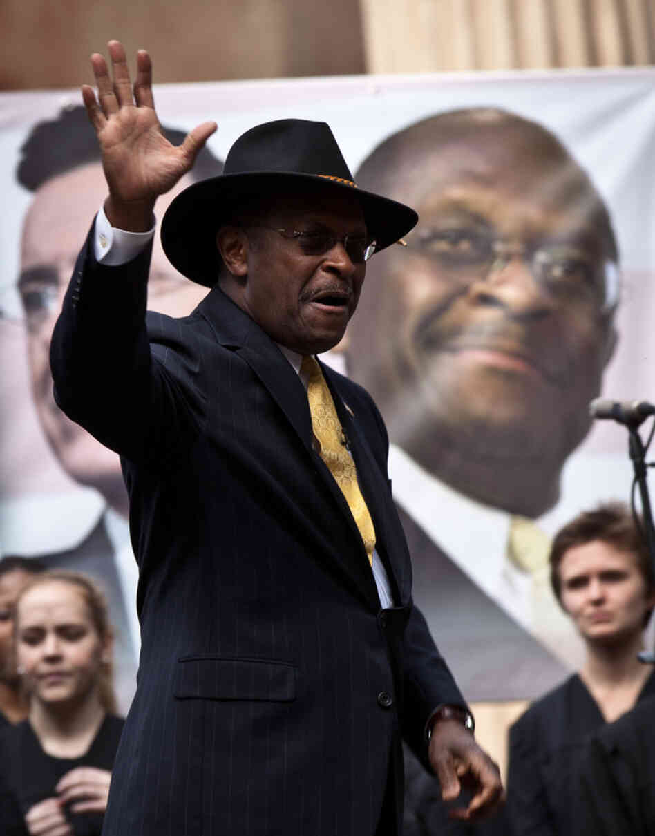 Former GOP presidential candidate Herman Cain waves at a rally the College of Charleston on January 20, 2012. Comedian Stephen Colb