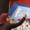 A student paints the Facebook logo on a mural commemorating Egypt's revolution last spring. The team from the CIA's Open Source Center monitors social media activity overseas.