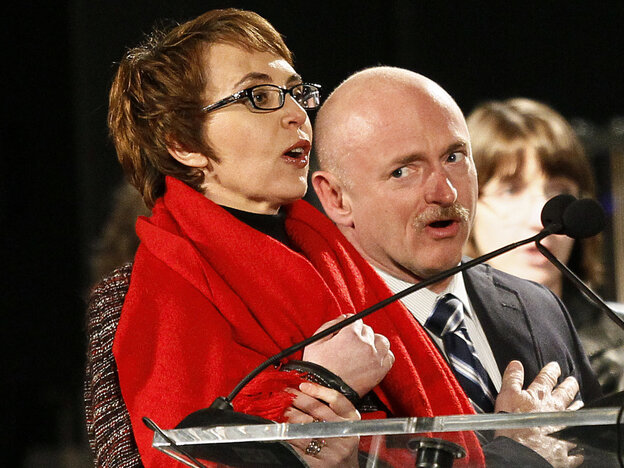 Rep. Gabrielle Giffords, with her husband, Mark Kelly, leads the Pledge of Allegiance at a Jan. 8 service to remember the Tuscon shooting victims.