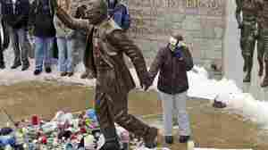 A woman pays her respects at a statue of Joe Paterno outside Beaver Stadium on the Penn State University campus in State College, Pa., after learning of his death on Sunday.