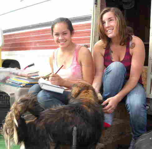 Eighteen-year-old Allie Neill and 20-year-old Eliza Aseltine sit on the front steps of Neill's family's RV in Slab City, Calif. Slab City is an informal, off-the-grid community in the California desert.